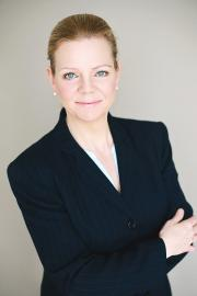 Headshot image of Carolyn Schwaar, facing camera in black jacket with tan background