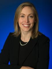 Headshot image of Katie Goldberg, smiling at the camera with a blue background