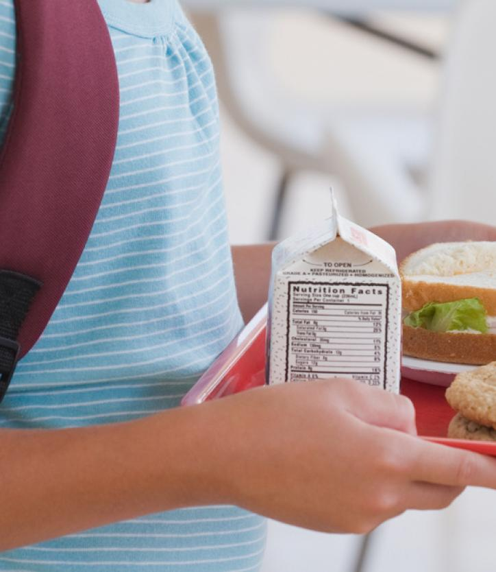 A child wearing a backpack and carrying a school lunch tray.