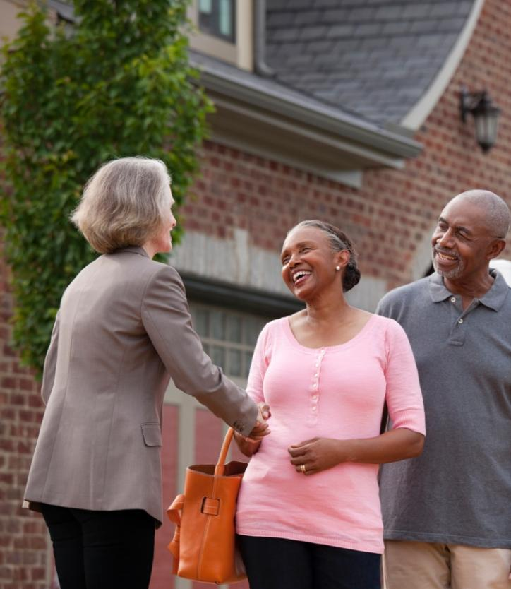 REALTOR® shaking hands with smiling couple outside house for sale