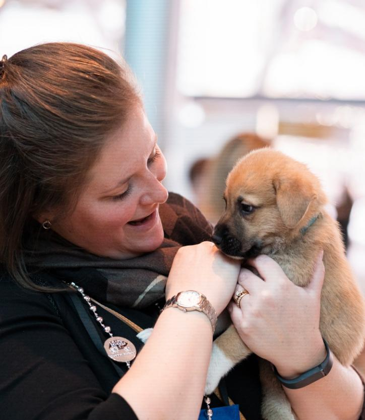 Woman holding golden retriever puppy, smiling