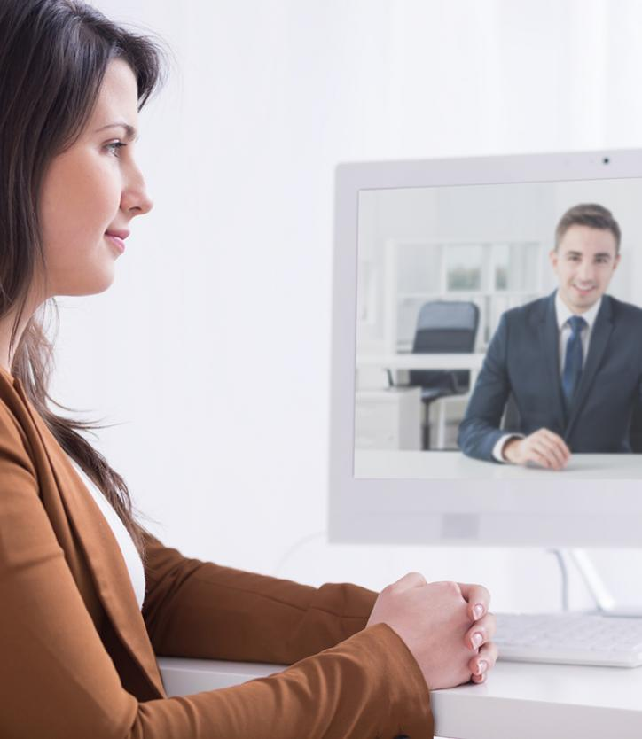 Woman Watching Meeting on Monitor