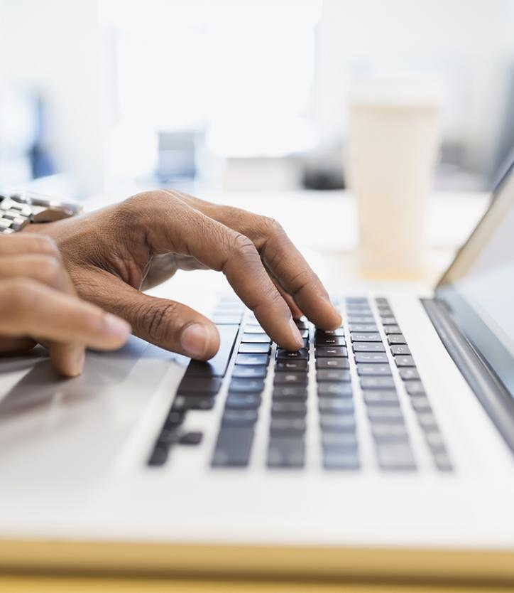 Businessman in a suit typing on a laptop