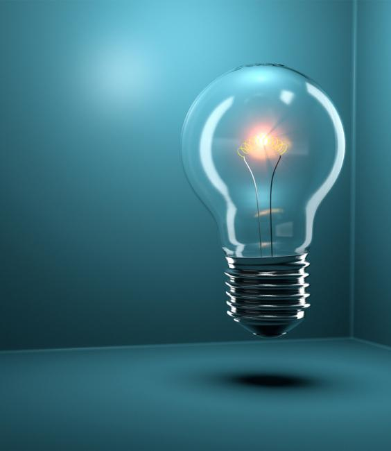 Light bulb glowing over a blue background.
