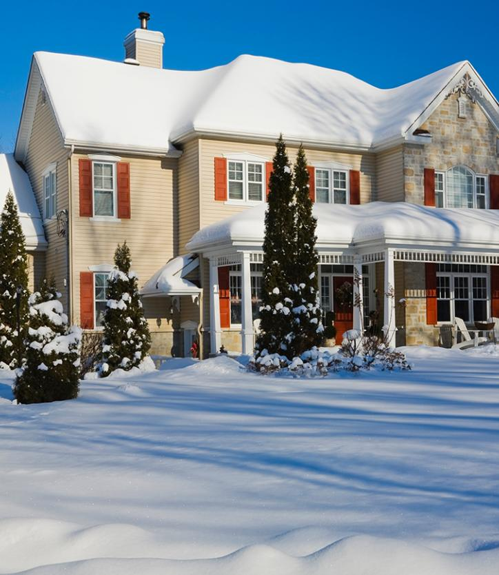 Large snow-covered tan house with red shutters
