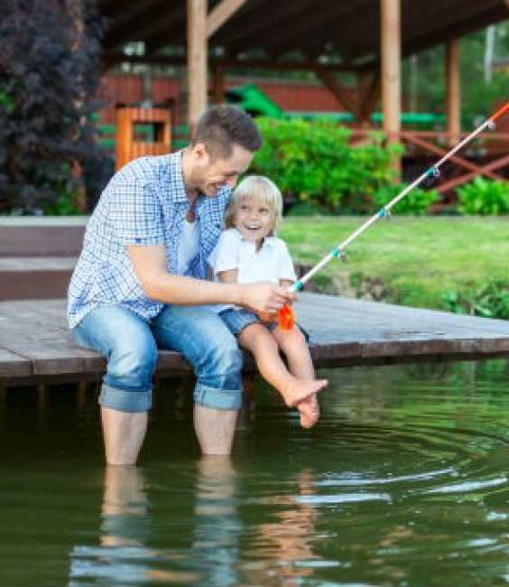Father and child fishing in lake by log cabin