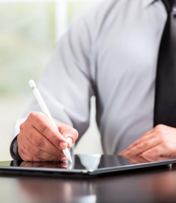 Man with tie signing document via table