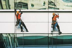 Window washers suspended on the side of a building