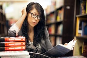 Business woman reading books in library
