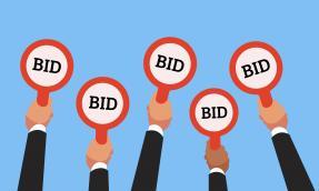 Buyers hands raising auction bid paddles