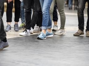 Group of people in jeans and sneakers walking in city