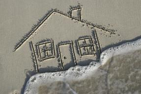 House in sand on beach flooded by wave