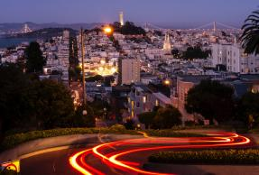 Early evening view of car light trail descending Lombard street in San Francisco with Telegraph Hill and Bay Bridge in distance.