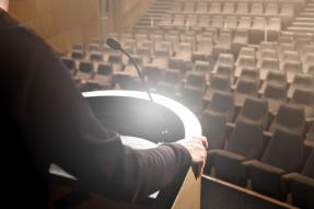 Close-up of unrecognizable man speaker on stage with microphone practicing in front empty seating in amphitheater