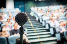 Microphone in auditorium with blurry crowd