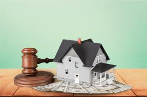 Mini house on top of cash with gavel