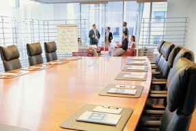 Board room table with members talking at end