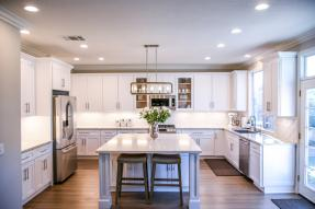 A kitchen in cold blue white trim with center island