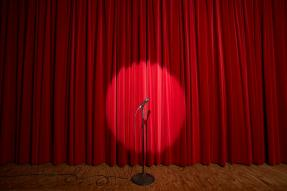 Spotlight on microphone stand on stage with red curtain