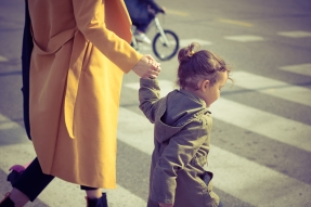 Adult and child crossing the street