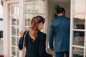 Agent and client entering a villa front door