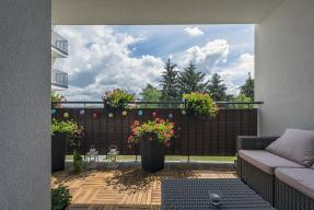 Apartment patio with blue sky and pine trees in the background