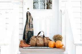 Duffel bag, jacket, boots, and pumpkins on a porch