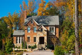 Brick house in wooded lot in autumn