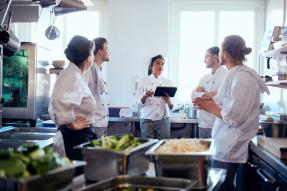Chef discussing with team in industrial kitchen