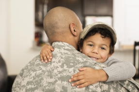 Child hugging man in camouflage clothing
