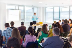 A conference speaker giving a presentation in a bright conference room with an audience.