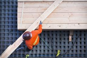 Construction worker carrying a board