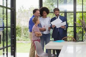 A family and a businessman looking at papers in a house