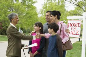 Family shaking hands with real estate agent