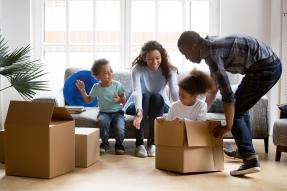 Family unpacking boxes in living room