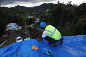 FEMA worker attaching a tarp to a roof
