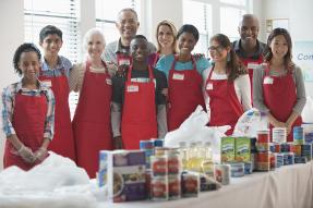 Food bank volunteers in red aprons