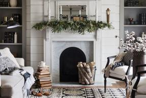 A green garland hangs over a white marble fireplace.