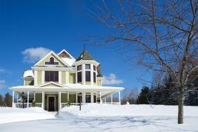 Green Victorian-style house in the snow