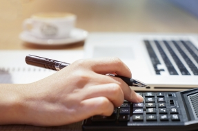 Hand with pen, calcualtor, papers, and laptop