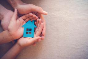 Hands holding a blue cutout of a house