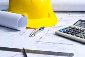 Hard hat, blueprints, and calculator