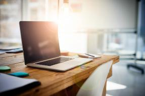 Laptop on Rustic Desk with Lens Flare