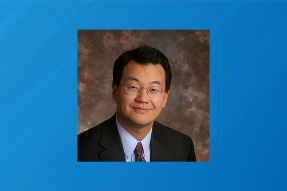Headshot of NAR Chief Economist Lawrence Yun on a striped blue background