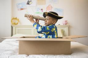 Little boy playing pirate in a moving box