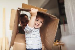 Little boy playing with moving box; father watching