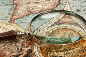 Magnifying glass on old world map