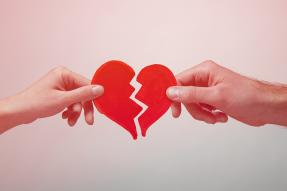 Male and female hands pulling a paper heart apart