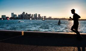 man jogging at sunset with boston skyline in background