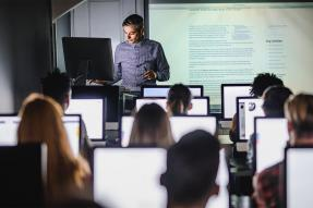 Man teaching a class of students at computers